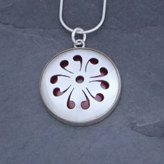 """Fire Within Pendant 3 from Sarah McCulloch Designs.  Empowering and bold, this pendant will surely express your unique spirit and passion. The pierced sterling silver reveals a layer of vibrant, flame-patinated copper. 1.25"""" in diameter and ⅜"""" deep, domed by hand and set in a sterling silver bezel. Available with a 16"""" or 18"""" sterling silver snake chain."""