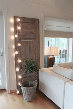 Idea: Find a tall standing object - bookshelf, standing mirror, door, and drape it with strand lights