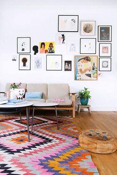 sala de estar decorada com tapete colorido, quadros com vários tamanhos na parede e molduras estreitas