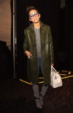 Zendaya Coleman attended the Rebecca Minkoff Fall 2014 Show in Vintage Dior Glasses, Rebecca Minkoff Fall 2013 toggle coat and black and white printed knee high boots. So what do you think was her look HOT or NOT?