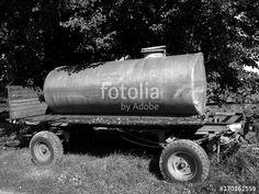 Alter Anhänger mit Wassertank und Patina am Barkhauser Weg in Oerlinghausen im Teutoburger Wald, fotografiert in neorealistischem Schwarzweiss