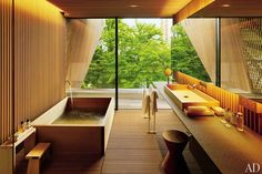 For a client in Japan, architect Kengo Kuma created a guest bath clad in wooden slats and with a striking window wall that lends the feeling of a tree house. The rectangular tub and basin are made of hiba wood and are offset by a sculptural stool.