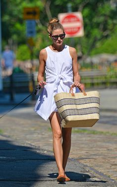 By day, Olivia Palermo accessorized her LWD with a straw tote and flats.