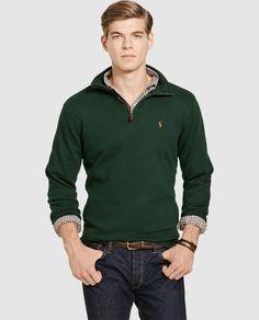 Jersey de punto liso y el cuello alto con cierre de cremallera. Tiene el logo de la firma bordado en el pecho.