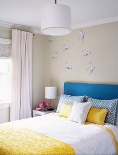 love the neutral walls with blue headboard, pillows.  And of course, the birds.