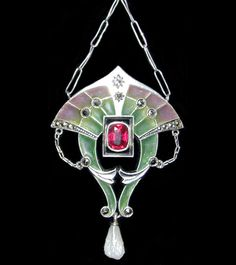 This is not contemporary - image from a gallery of vintage and/or antique objects. CARL HERMAN (Herman and Speck. Pforzheim) (Attrib.)  A silver; plique-a-jour pendant set with a central red paste stone and marcasites, with a pearl drop.