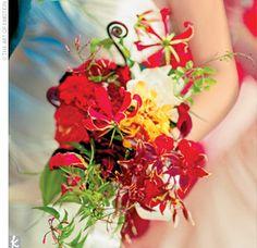 Erika carried a bouquet of gloriosa lilies, roses, stephanotis, burgundy mini calla lilies, gardenias, chocolate cosmos, fern fiddleheads, and burgundy orchids.