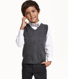 Three-part set containing a shirt, slipover and a bow tie or tie. The shirt is in a cotton weave with a narrow turn-down collar and long sleeves. The slipover is in a fine knit with a V-neck. The pre-tied tie/bow tie has adjustable elastication and a plastic fastener at the back of the neck.