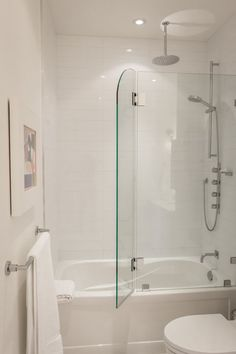 Master Bathroom *white, bright, short tub, tile to ceiling, shower shield* via House Tour - Greg & Rob's Sky Suite | Apartment Therapy | by Palmerston Design Consultants
