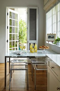A stainless steel parsons dining table is lined with see through acrylic dining chairs, CB2 Vapor Chairs which sit under a window dressed in a cream roman shade accented with gray trim.