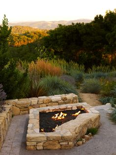 A large, stone fire pit creates a cozy outdoor space ideal for entertaining year round. A wrap-around stone bench offers plenty of seating that looks out to exquisite mountain views.