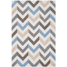 Anchor your dining set or living room seating group in eye-catching style with this hand-tufted wool rug, showcasing an chevron motif.