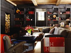 Dark Americana living space with red accents for the gentleman - firewood, books, library lights, ottoman, wool throws, rustic wood ceiling - Elle Decor