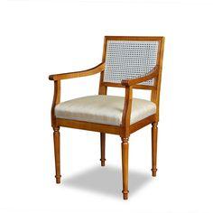 Der Louis Seize Armlehnstuhl ist aus massiver Kirsche gefertigt und besitzt neben einer gepolsterten Sitzfläche eine Rückenlehne aus Wiener Geflecht.