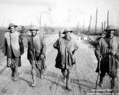 WWI: Four Canadian Highlanders smile as they walk along a muddy path away from the front lines. Kilts and bare knees can be seen beneath the veneer of mud. The three soldiers on the right wear respirator bags slung across their chests; all four wear the popular sleeveless leather jerkin. - Found via Canada at War