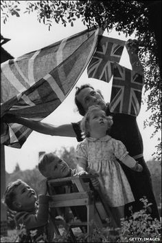 Young children help put up bunting and flags on VE Day in London.
