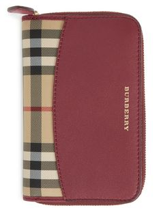 Dark plum leather gorgeously accents Burberry's Horseferry check on this luxe zip-around wallet.