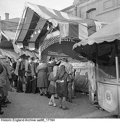 Reference No. Children gathered around a rifle range at the the Easter fair on the site of the cattle market, Norwich, Norfolk Date 25 Mar 1948 Photographer: Hallam Ashley Historical Images, Norwich Norfolk, England, Street View, Cattle, Building, Easter, Travel, Range