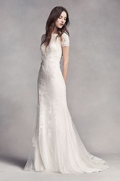 Effortlessly chic and modern. This veiled lace short sleeve sheath wedding dress is thoughtfully detailed with corded lace and delicate organza flowers. A bias-cut charmeuse slip is layered underneath