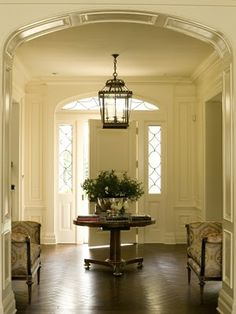 The paneled entry hall features an oversized front door with leaded glass sidelights and traditionally detailed arched transom. Herringbone walnut flooring helps to unite two strong cross axes of the space. House Design, House, Hall Lighting, Home, Entry Foyer, Foyer Decorating, Entrance Doors, House Interior, Interior Design