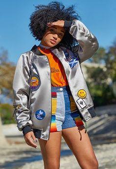 Amandla Stenberg wearing a greay Hunter bomber jacket with patchwork denim shorts