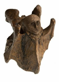 Large animal lumbar vertebra carved with at one end with a human face. Used as a household talisman.
