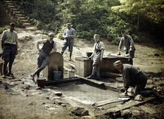 World War I in Color: Six French soldiers with buckets and laundry at a fountain, 1917.
