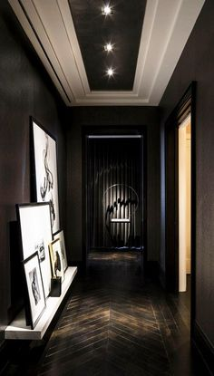 Black hallway with wooden herringbone floor design.