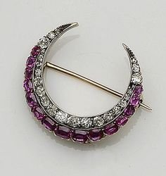 A ruby and diamond crescent brooch, circa 1890  The row of cushion-shaped, rose and old brilliant-cut diamonds to an oval and circular-cut ruby border, mounted in silver and gold, (one diamond deficient), total diamond weight approximately 0.55ct, length 2.9cm.