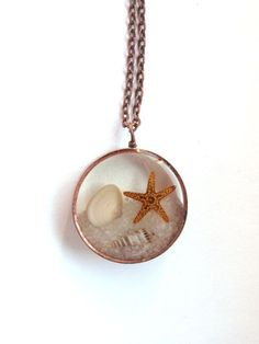 At the Beach Pendant - Sand, shells, and starfish encased in resin with antique copper open back bezel on Etsy, $12.50
