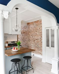 An exposed brick wall in the kitchen lends unique charm and dimension to the space. See how Chris Loves Julia overhauled this kitchen for less than $5k.