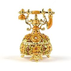 """Old Fashioned Telephone Trinket Box Item No. KB00610A01 $30.79 Call home! This golden Faberge style trinket box in a shape of old fashioned telephone is pewter molded. The box is hand enameled, and decorated with Austrian crystals. This box is hinged, and features a magnet for a clasp. The magnet enables the box to open easily, but close firmly. It has a strong magnet to hold the two halves together. It also features gold accented trim work and the egg comes complete in a satin-lined gift… Trim Work, Amber Jewelry, Austrian Crystal, Trinket Boxes, Gold Accents, Telephone, Pewter, Organize, Two By Two"