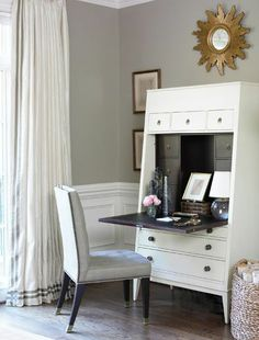 Chic gray office design with gray walls paint color, wainscoting, gold sunburst mirror, white secretary cabinet, gray tufted chair and white silk curtains window panels with gray silk ribbon border trim..