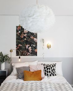 White room and bed with pretty throw pillows and a gold wall sconce. I'm love it !