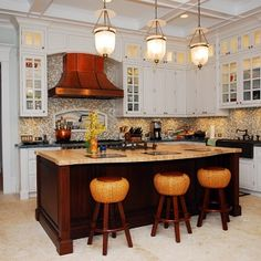 Use of copper and bronze in white kitchen; pendant lights. Stools are awful.