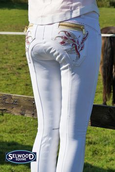 Animo Nagor Ladies Full Seat Breeches White These Animo Nagor full seat breeches with red stitched and studded patterns on the back pockets, along with the gold zip above the pocket create a striking effect. Featuring delicate Swarovski crystal and embroidery design on the back pockets adding sparkle as well as a beautiful edge to any competition outfit. These breeches are machine washable at 30 degrees.