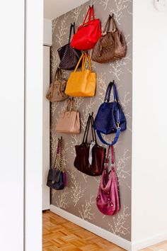designed a handbag wall for a client who loved and collects designer handbags on an under utilized wall across from the bathroom, but close the apartment's front door to keep her streamline when leaving for work.  Since it is a rental, I used temporary vinyl wallpaper to separate it from the other white walls.