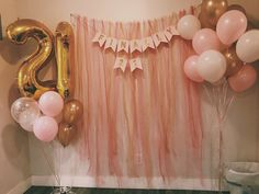 DIY photo backdrop made out of different tulle. 3 shades of pink, gold, and white. Just cut the pieces of tulle to the same length and used a needle and yarn to string together!