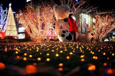 a chinese girl poses for photographs next to elaborate christmas decorations in a shopping centre in