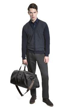 Camisa marinho, cardigan cinza e marinho, calça grafite chino e sapato brogue. A mala em nylon com couro é ótima para as viagens de final de semana.