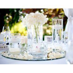 Un magnifique miroir rond sert de base a un cenrte de table créé avec quelques photophores en verre carrés, et quelques vases cylindriques en verre: Chaque vase est décoré de roses blanches, de bougies flottantes, de fleurs d'orchidées blanches, et du'n bouquet plus grand