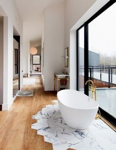 Modern bathroom with a freestanding tub, and a large window