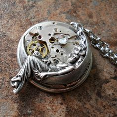 "A wonderfully detailed sterling silver plated stamping of an other-worldy goddess reposing on her cresent moon is mounted onto a vintage round watch movement with loads of mechanical detailing for steampunk industrial chic. The watch movement is embellished with a Swarovski rhinestone ""star"" for a bit of shine and is mounted into a round sterling silver plated round setting for a nice finished look. The pendant measures 1- inch in diameter and finishes with an antiqued silver 18-inch chain."
