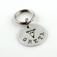 This custom dog tag is a one-of-a-kind design by me featuring a greyhound face. This design is made from stamping individual letters and symbols, so each one will be different.  A 3/4 sterling silver disc will be hand stamped with your dogs name curving underneath my dog face design. Pet names up to 8 characters will fit. If you need more room, convo me and well figure it out. Since the disc is nice and thick, I can stamp your phone number on the back.  The tag then hangs from split rings…