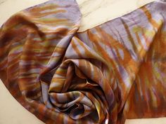 A very pretty 100% silk scarf. Hand painted with a cool lavender and yellows, golds, oranges and copper. A beautiful combination of rich colors. Hand rolled hems. 8mm Habotai silk Approximately 58.5 x 15.0 Hand wash in cool water with delicate fabric detergent. Use a bit of Fabric
