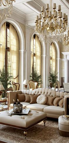 Glam luxe living room...really over the top but digging the huge arched windows fab tufted sofa and all in monochromatic beiges..