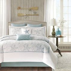 A soft seafoam blue is the accent color used in this beach themed king-size comforter and shams playing up the seashell and sand dollar embroidery. #romanticcoastalbedrooms