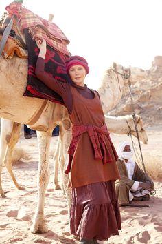 """rotes Trägerkleid aus Fischgrätgewebe:  In der Wüste """"Wadi Rum"""" vor den Kamelen des Beduinen Mohammad präsentiert das Model ein rotes Trägerkleid aus Fischgrätgewebe, das vorne eine hübsche Stickerei hat. Um die Hüfte gebunden trägt sie eine Baumwollstrickjacke und unter dem Kleid einen farblich abgestimmten Rock."""