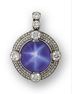 An art deco star sapphire and diamond pendant/brooch, circa 1930  centering a round cabochon star sapphire within a double-row surround of single-cut diamonds, accentuated by four old European-cut diamond collets, suspended from a detachable diamond two-stone surmount; sapphire weighing approximately: 37.00 carats; estimated total diamond weight: 5.50 carats; mounted in platinum