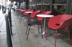Uni-Ka 563-P in Red at Bors Cafe. Finland. Stackable armchairs with padded-effect polypropylene shells on steel legs. Exterior Design.